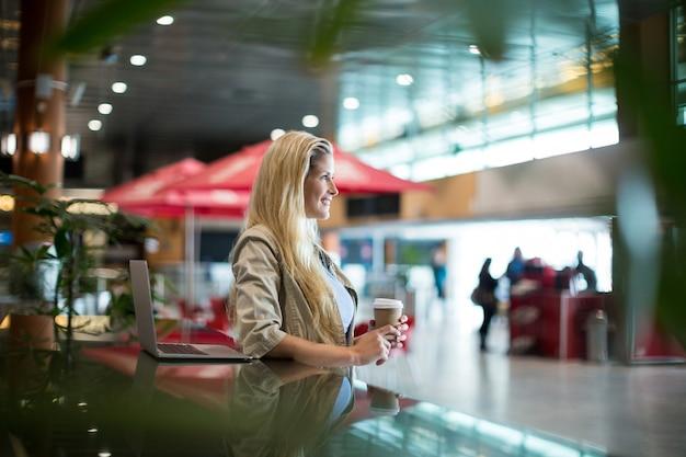 Uśmiechnięta kobieta z kawą stojącą w poczekalni