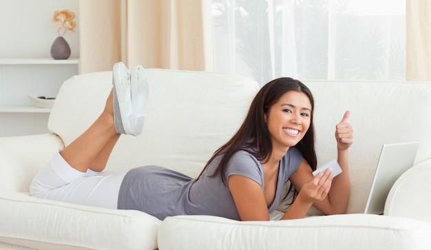 Uśmiechnięta kobieta z kciukiem do góry i karty w ręku leżąc na kanapie patrząc na kamery