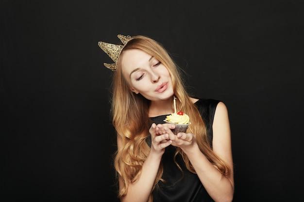 Uśmiechnięta kobieta z koroną, trzyma urodzinową babeczkę