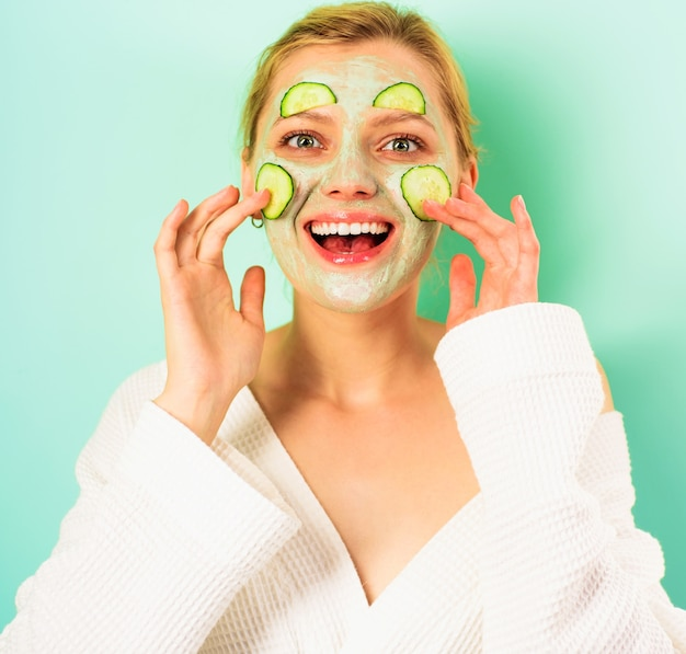 Uśmiechnięta kobieta z kosmetyczną maską na twarzy. szczęśliwa dziewczyna z maską na twarz. zabieg upiększający. terapia uzdrowiskowa. zabiegi kosmetyczne.