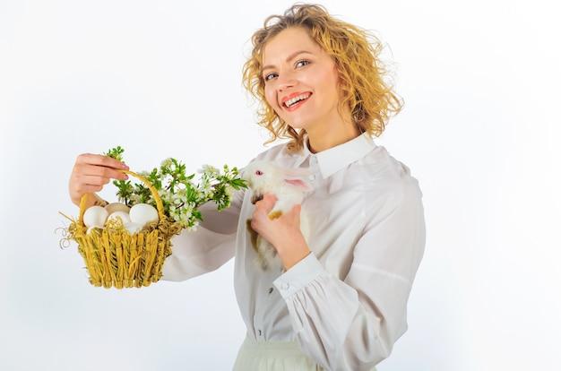 Uśmiechnięta kobieta z koszykowymi jajkami i królikiem wielkanocnym