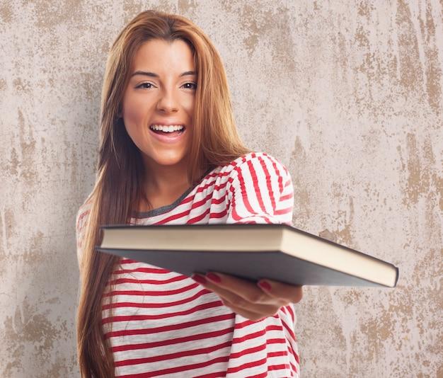 Uśmiechnięta kobieta z książki na teksturą ścianie