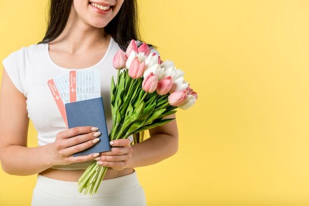 Uśmiechnięta kobieta z kwiatami i biletami samolotowymi