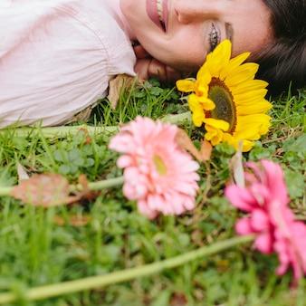 Uśmiechnięta kobieta z kwiatami na trawie