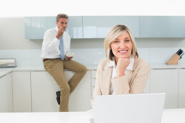 Uśmiechnięta kobieta z laptopem i mężczyzna w tle przy kuchnią