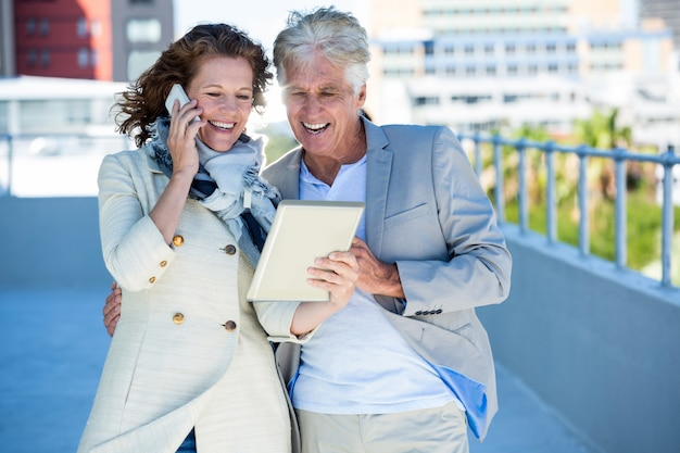 Uśmiechnięta kobieta z mężczyzna używa cyfrową pastylkę