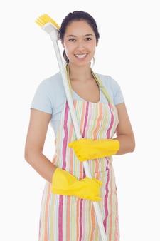 Uśmiechnięta kobieta z miotłą na jej ramieniu