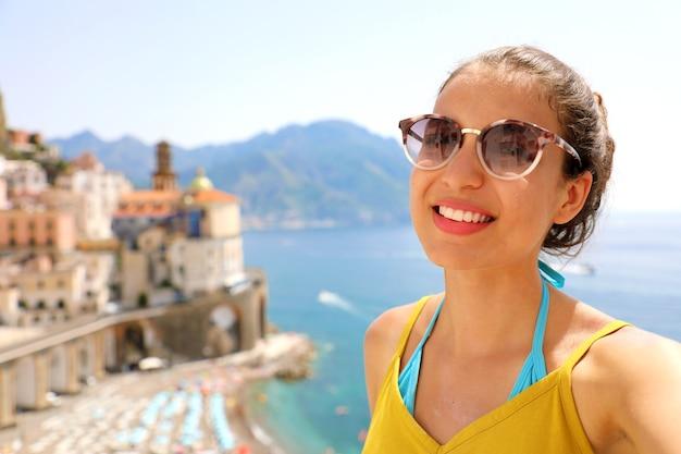 Uśmiechnięta kobieta z okularami przeciwsłonecznymi w wiosce atrani, wybrzeże amalfi we włoszech