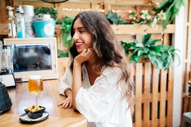 Uśmiechnięta kobieta z oliwek i piwa