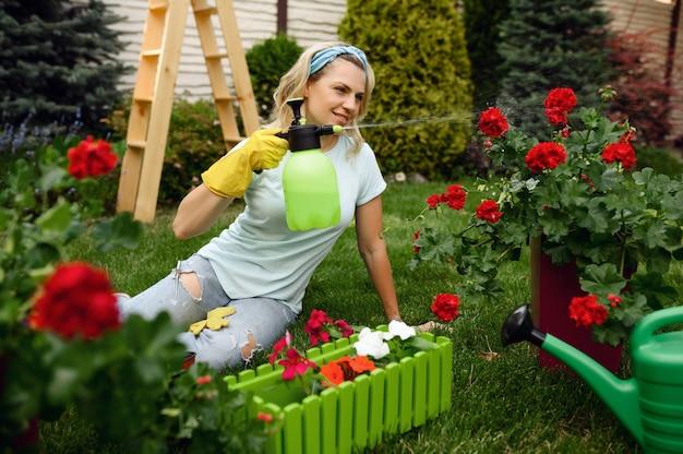 Uśmiechnięta kobieta z opryskiem podlewania kwiatów w ogrodzie