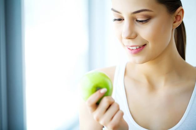 Uśmiechnięta kobieta z pięknym uśmiechem, białe zęby trzyma jabłko. obraz w wysokiej rozdzielczości