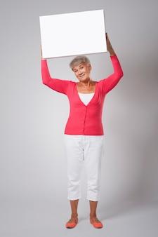 Uśmiechnięta kobieta z pustą tablicą