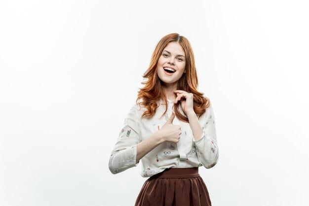 Uśmiechnięta kobieta z rudymi włosami w świetle modelu garnituru.