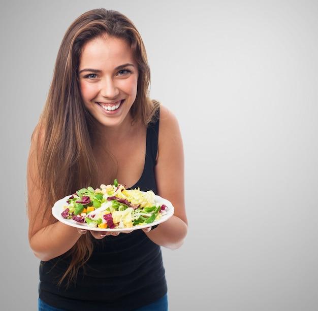 Uśmiechnięta kobieta z sałatką w ręce