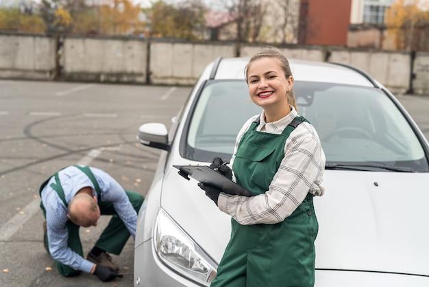 Uśmiechnięta kobieta z schowkiem i pracownik zmienia koło samochodu