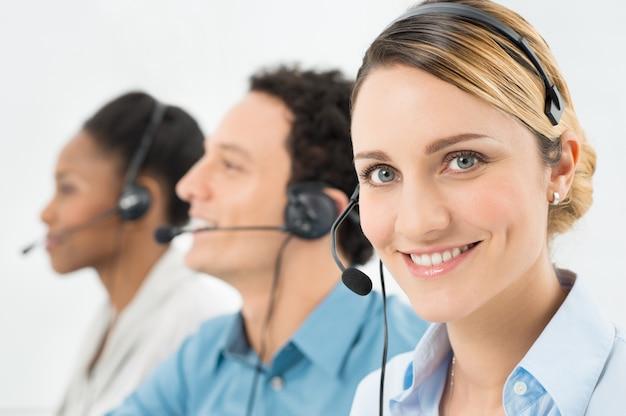 Uśmiechnięta kobieta z słuchawki pracujące z innymi współpracownikami w call center