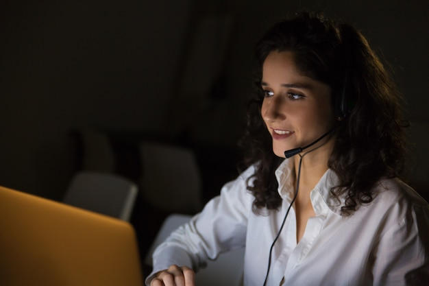 Uśmiechnięta kobieta z słuchawki w ciemnym biurze