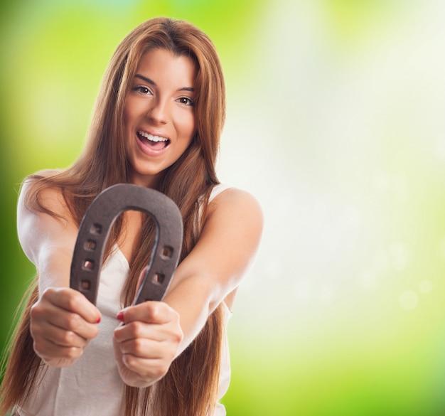 Uśmiechnięta kobieta z symbolem szczęścia konia buta