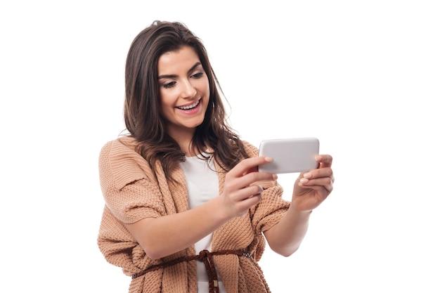 Uśmiechnięta kobieta z współczesnym telefonem komórkowym