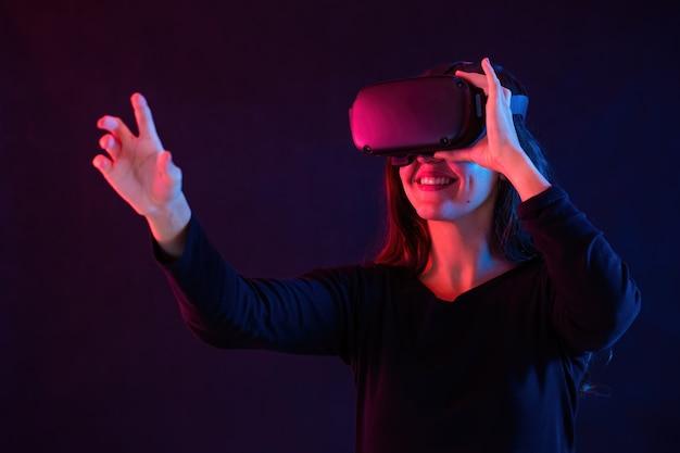 Uśmiechnięta kobieta z zestawem słuchawkowym interakcji w wirtualnej rzeczywistości