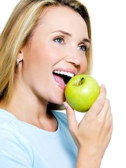 Uśmiechnięta kobieta z zielonym jabłkiem - na białym tle