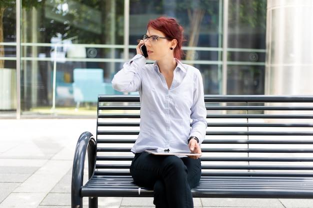 Uśmiechnięta kobieta za pomocą cyfrowego tabletu na zewnątrz, siedząc na ławce i rozmawiając przez telefon