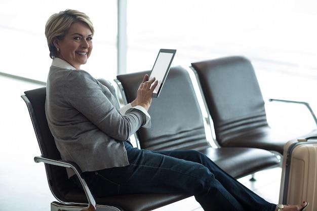 Uśmiechnięta kobieta za pomocą cyfrowego tabletu w poczekalni
