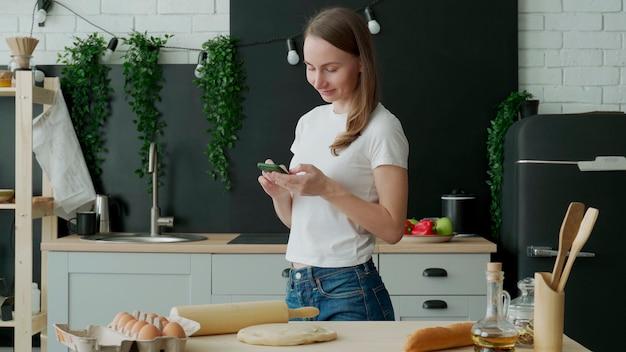 Uśmiechnięta kobieta za pomocą inteligentnego telefonu w kuchni