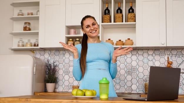 Uśmiechnięta kobieta za pomocą komputera w nowoczesnych wnętrzach kuchni. gotowanie i koncepcja zdrowego stylu życia. kobieta nadaje w internecie i gestykuluje emocjonalnie