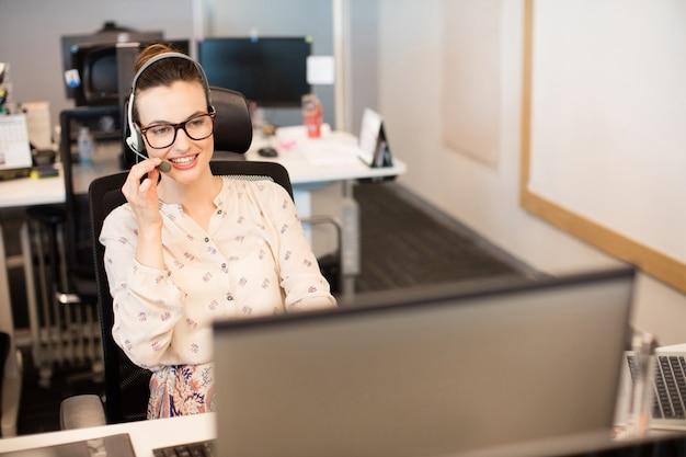 Uśmiechnięta kobieta za pomocą zestawu słuchawkowego w biurze