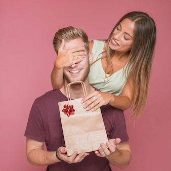 Uśmiechnięta kobieta zakrywa jej chłopaka oko daje on prezentowi torba na zakupy