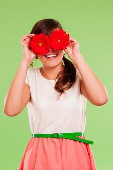 Uśmiechnięta kobieta zasłaniając oczy dwoma kwiatami