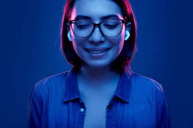 Uśmiechnięta kobieta ze słuchawkami tws słuchać muzyki