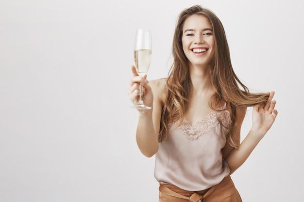 Uśmiechnięta kobieta zmysłowa zabawa z lampką szampana