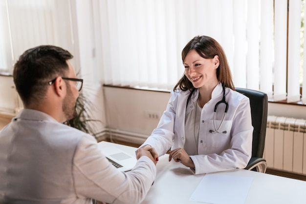 Uśmiechnięta kobiety lekarka przy kliniką daje uściskowi dłoni jej pacjent