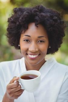 Uśmiechnięta kobiety mienia herbata w ogródzie