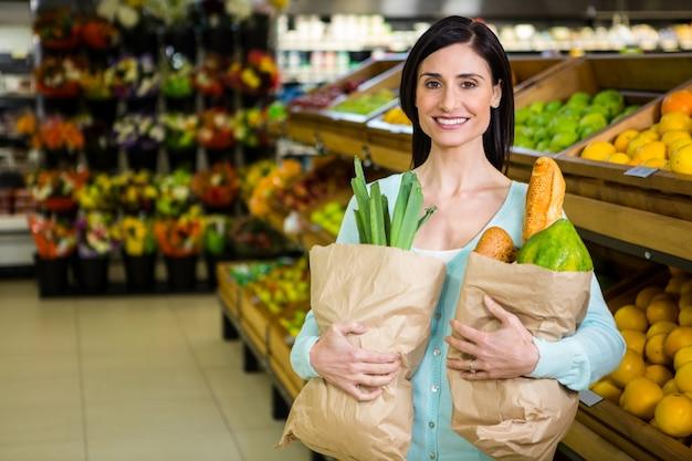 Uśmiechnięta kobiety mienia sklepu spożywczego torba