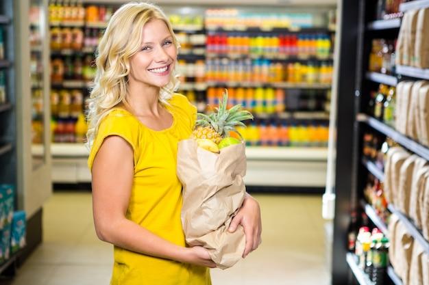 Uśmiechnięta kobiety pozycja w nawie z sklep spożywczy torbą