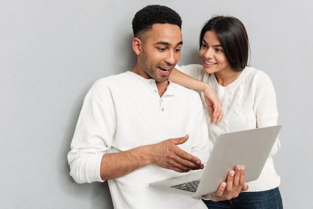 Uśmiechnięta kochająca para gawędzi laptopem.
