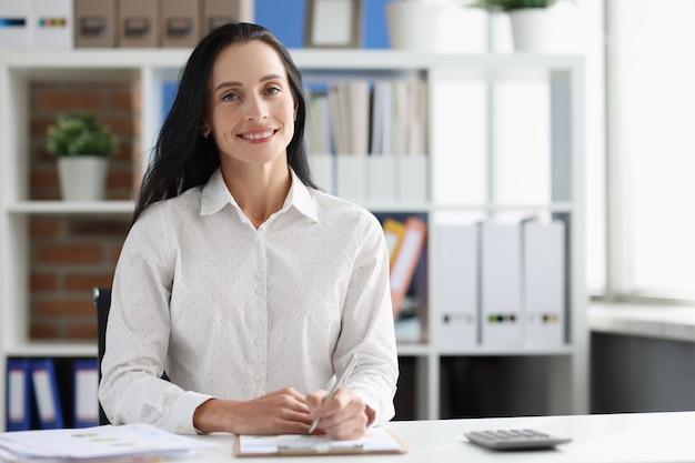Uśmiechnięta konsultantka biznesowa przy stole roboczym w koncepcji marketingu biurowego zawodu
