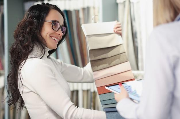 Uśmiechnięta konsultantka pokazuje próbki tkanin kupującemu wybór materiału do szycia