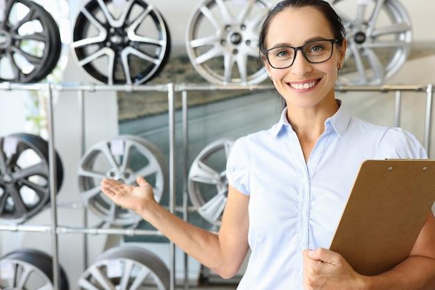 Uśmiechnięta konsultantka rekomenduje wybór felg do samochodów koncepcyjnych