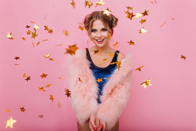 Uśmiechnięta kręcona dziewczyna w modnym płaszczu przygotowała świąteczną niespodziankę na przyjęcie urodzinowe przyjaciela. śmiejąc się niesamowita młoda kobieta z radością pozuje z konfetti złotym brokatem stojąc na różowym tle