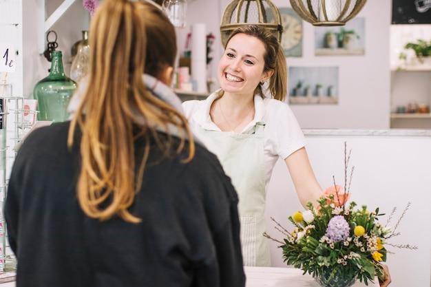 Uśmiechnięta kwiaciarnia opowiada z klientem