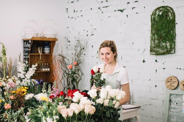 Uśmiechnięta kwiaciarnia z bukietem patrzeje kamerę