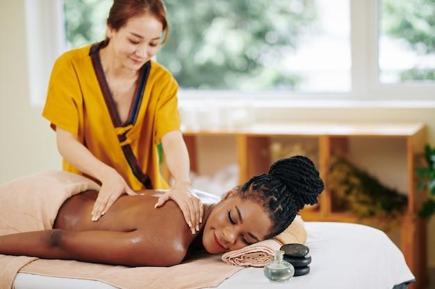Uśmiechnięta ładna afro-amerykańska kobieta podczas masażu ciała w salonie spa