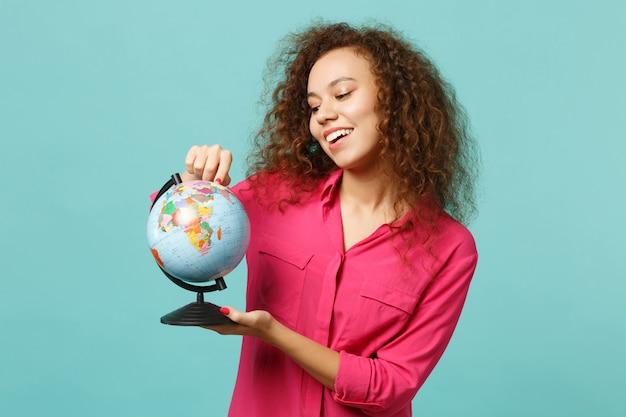 Uśmiechnięta ładna afrykańska dziewczyna w ubraniach casual, wskazując palcem wskazującym na kuli ziemskiej ziemi na białym tle na niebieskim tle turkusu w studio. ludzie szczere emocje, koncepcja stylu życia. makieta miejsca na kopię.