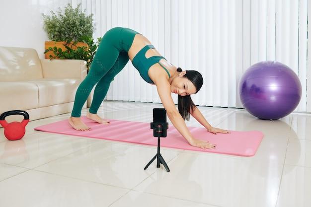 Uśmiechnięta ładna azjatycka blogerka fintess prowadząca zajęcia jogi online dla swoich subskrybentów i robiąca pozę psa zwrócona w dół przed smartfonem