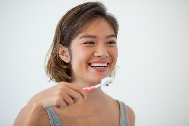 Uśmiechnięta ładna azjatycka kobieta szczotkuje zęby