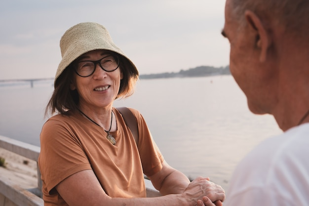 Uśmiechnięta ładna azjatycka starsza kobieta w kapeluszu i okularach z mężem na gałęzi morza lub rzeki w lecie